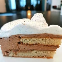 coupe d'une part de pouchkine avec son biscuit amande café alterné de mousse au café et chocolat au lait surmonté de chantilly